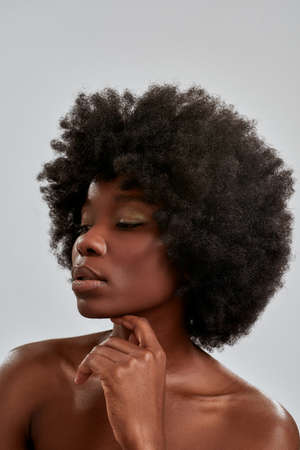 Portrait of beautiful african american woman with afro hair and perfect glowing skin looking aside, posing isolated over gray background