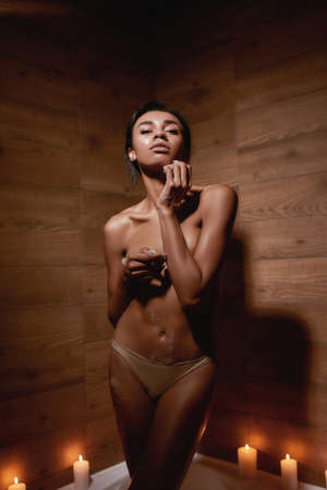 She making me crazy. Vertical shot of a young beautiful and sensual mixed race nude woman standing in the bath with candles and looking passionate at camera