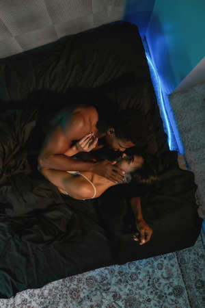 Top view of a young beautiful mixed race couple enjoying sensual foreplay before making love in bedroom at home, vertical shot