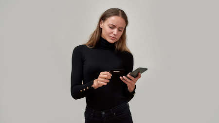 Focused young woman wearing black clothes looking at credit card, using smartphone while posing isolated over gray background