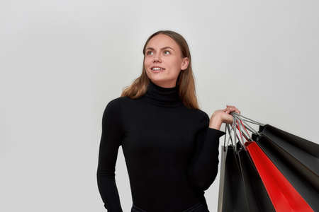 Studio shot of pretty young caucasian woman wearing black clothes looking dreamy, holding bunch of shopping bags while posing isolated over light gray background