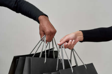 Close up shot of female and male hands holding black paper bags after doing shopping together isolated over light background