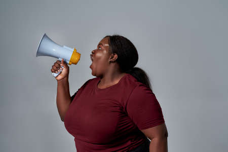 Emotional plus size african american woman in casual clothes looking away, screaming using megaphone, posing isolated over gray background