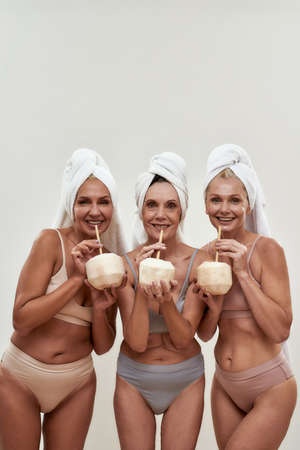 Women in a good mood sipping drink from young coconuts