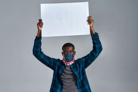 Young african american guy wearing bandana mask looking at camera, holding blank white banner ad above his head, asking for support, posing isolated over gray background