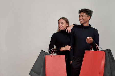 Casual couple of shoppers, friends wearing black clothes smiling aside, holding many colorful shopping bags, posing isolated over light gray background 免版税图像