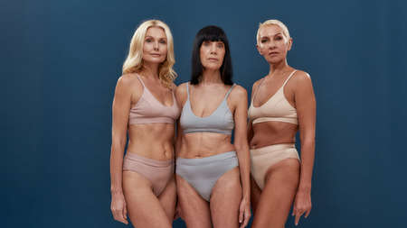Mature models. Three attractive caucasian senior women in underwear looking at camera while posing half naked in studio against dark blue background