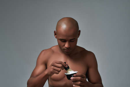 Shirtless handsome young african american man looking focused, using brush while making shaving foam, posing isolated over gray background 免版税图像
