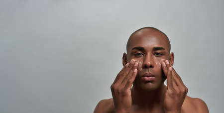 Portrait of handsome young african american man looking at camera, applying cream on his face, posing isolated over gray background