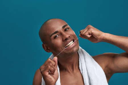 Multiracial person placing a dental cord to his teeth 免版税图像