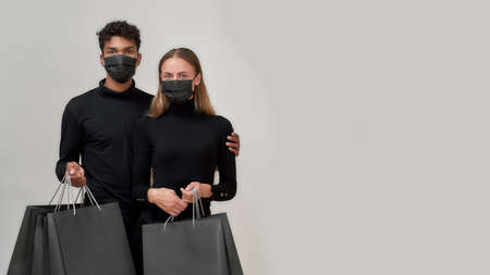 Best friends wearing black outfits and protective masks looking at camera, holding shopping bags, posing together isolated over light gray background