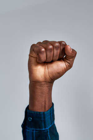 Close up shot of raised fist of african american guy in checkered shirt posing isolated over gray background
