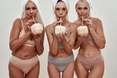 Women drinking through straws from peeled coconuts 免版税图像