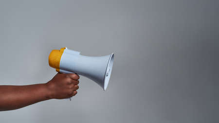 Closeup shot of female hand holding megaphone isolated over gray background