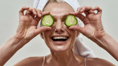 Satisfied female with opened mouth holding cucumber circles