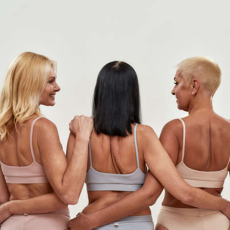 Mature caucasian women in underwear embracing each other and smiling while standing isolated over light background