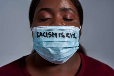 Close up shot of young african american woman wearing protective face mask with Racism is evil text posing with eyes closed isolated over gray background
