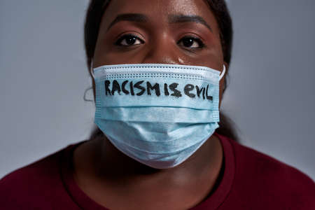 Close up shot of young african american woman wearing protective face mask with Racism is evil text looking at camera, posing isolated over gray background 免版税图像