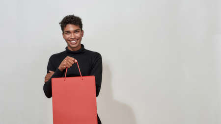 Happy african american guy holding shopping packet 免版税图像