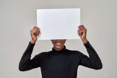 Cheerful young african american man hiding behind poster