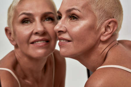 Mature female pressing cheek to a mirror 免版税图像