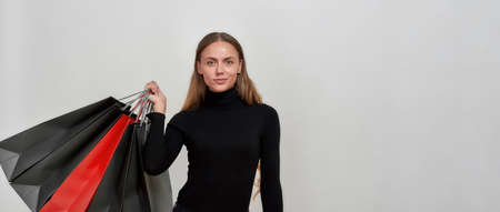 Studio shot of attractive young caucasian woman wearing black clothes looking at camera, holding bunch of shopping bags while posing isolated over light gray background