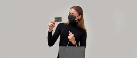 Fashionable young woman wearing black protective mask holding plastic credit card while posing with shopping bag isolated over gray background 免版税图像