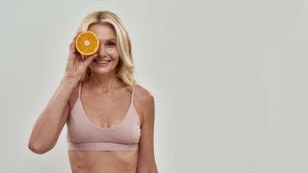 Beautiful lady keeping fruit before right eye 免版税图像