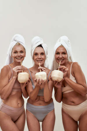 Female friends giggling while drinking from coconut