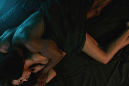 Young african naked man kissing his sleeping girlfriend while relaxing after amazing sex, couple sleeping together in bedroom