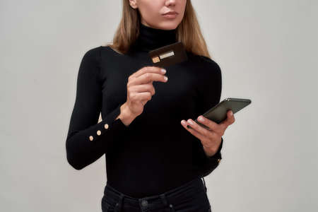 Cropped shot of caucasian young woman wearing black clothes holding credit card, using mobile phone while posing isolated over gray background