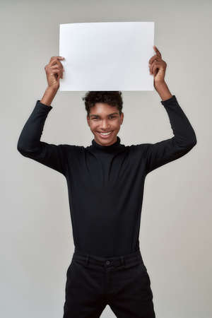 Young african american man holding empty poster above his head