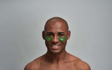 Man with self-assured smile in under eye patches