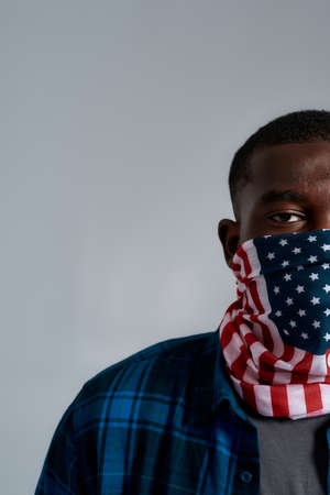Half face portrait of young african american male protester, activist wearing bandana mask with american flag print while posing isolated over gray background