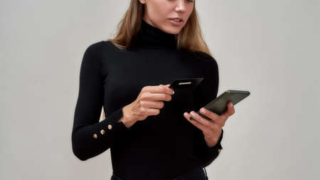 Cropped shot of caucasian young woman wearing black clothes holding credit card, using smartphone while posing isolated over gray background