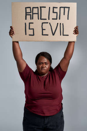 Fierce plus size young african american woman in casual clothes looking at camera, holding Racism is evil banner above her head, posing isolated over gray background