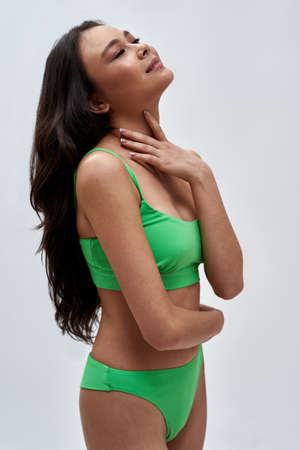 Portrait of sensual young woman wearing green underwear looking up with a smile, posing isolated over light background