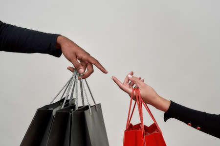 Close up shot of female and male hands holding black and red paper bags, reaching for each other isolated over gray background