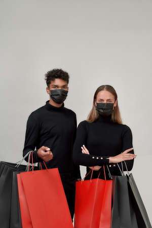 Couple of friends wearing black outfits and protective masks looking at camera, holding bunch of shopping bags, standing isolated over light gray background 免版税图像