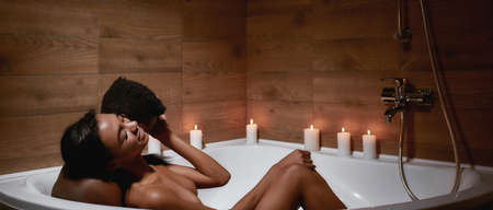 Language of feelings. Young african man kissing his girlfriend in neck while taking foamy bath with candles together at home