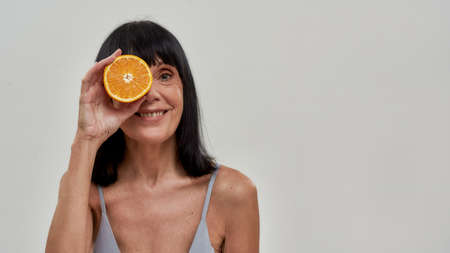 Optimistic woman holding cut orange in front of her eye