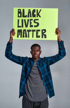 Confident young african american guy in casual clothes looking at camera, holding demonstration banner with BLM text above his head, posing isolated over gray background