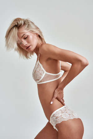 Young sensual woman with slim body wearing white lingerie looking while posing isolated over grey background