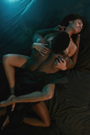Sex life. Top view of a passionate mixed race couple, man and woman making love while lying on the bed