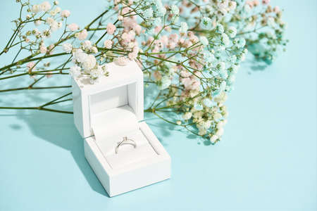 Romantic surprise for her. White gift box with engagement diamond ring and beautiful fresh spring flowers on blue background 免版税图像