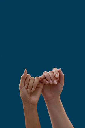 Close up of two hands hooking each other little finger pinkie as a symbol of promise or pardon isolated on blue background