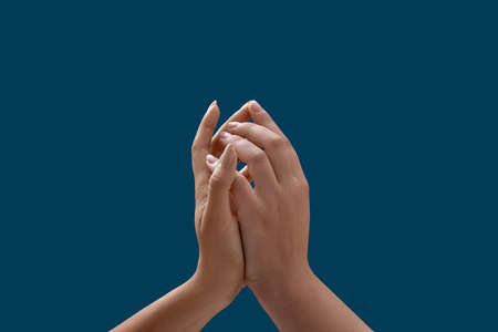 Close up of two female hands touching each other uniting isolated on blue background