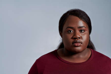 Close up portrait of calm plus size young african american woman in casual clothes looking at camera