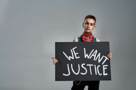 Cool tattooed young caucasian female activist looking at camera, holding cardboard banner with We want justice text, posing isolated over gray background