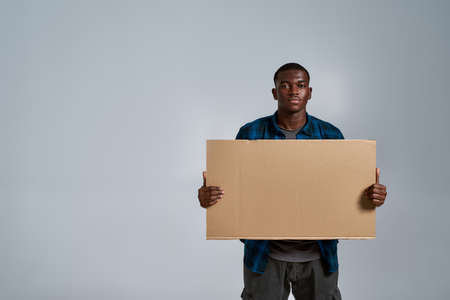Serious young african american man in casual clothes looking at camera, holding blank banner ad in front of him, posing isolated over gray background